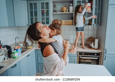 Attractive young woman and her two little cute daughters have fun in the kitchen