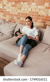 attractive young woman holding book near black french bulldog