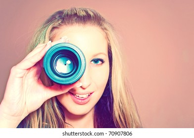 Attractive young woman holding camera lens like it was spyglass