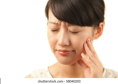 Attractive young woman holding her hand on her aching tooth