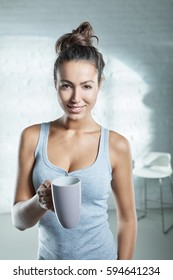 Attractive young woman holding morning tea, smiling happy.