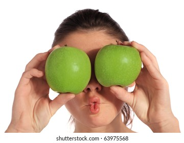 Attractive young woman holding two green apples in front of her eyes. All on white background.
