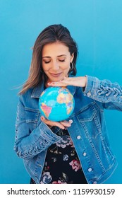Attractive young woman holding a world globe balanced between her hands with a smile against a blue exterior wall