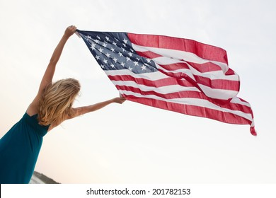 Attractive young woman holds high an American Flag while standing on the beach