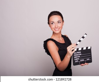 An attractive young woman holds an open film slate
