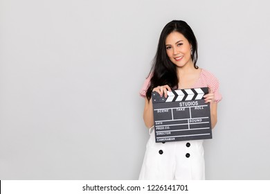 An attractive young woman holds an open film slate on gray background