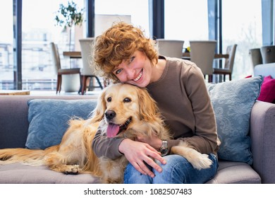 Attractive young woman hugging her dog and smiling Indoor Cafeteria