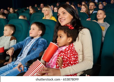 Attractive young woman hugging her cute little daughter smiling joyfully watching cartoon together at the cinema copyspace family parents mother kids childhood positivity leisure concept.