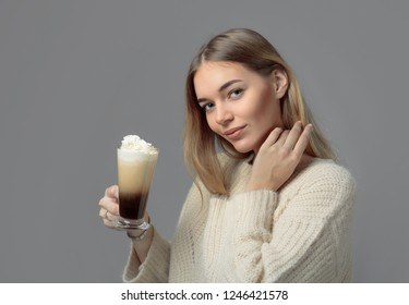 Attractive young woman with Irish coffee. Beautiful blonde in a sweater holding a mug of coffee with cream. Copy space.