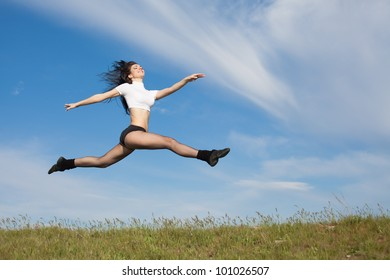 Attractive young woman jumping on open air. Brunette jumps on background of sky