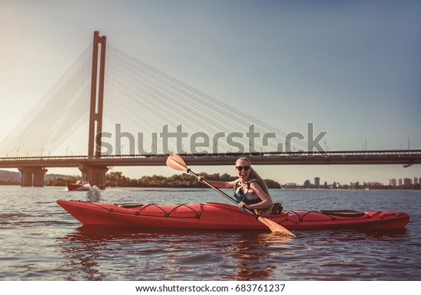 Attractive young woman is kayaking on sunset. Canoeing alone.