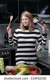 Attractive, young woman with kitchen utensils in her hands stands in the kitchen