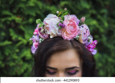 Attractive young woman with large pink flowers crown