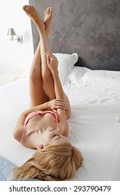 Attractive young woman laying on a bed at home in lingerie, applying hydrating lotion on her legs with her hand, interior. Girl caring for her skin in underwear. Health and well being beauty indoors.
