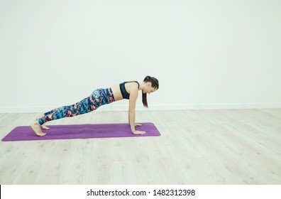 Attractive young woman leaning on her hands doing exercise at gym. copy space
