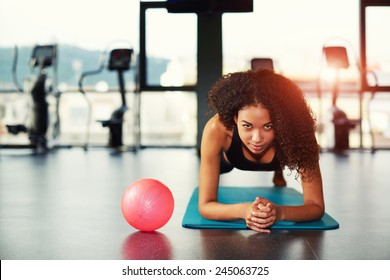Attractive young woman leaning on her elbows doing exercise for buttocks muscles at gym
