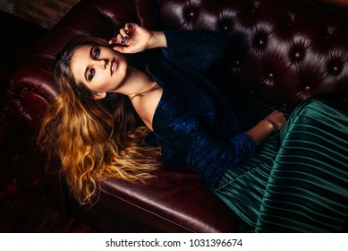 Attractive young woman lies on a leather sofa in a stylish clothes. Beauty, fashion. Evening makeup and hairstyle.