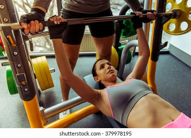 Attractive young woman lifting weight in gym, handsome muscular trainer helping her