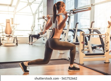Attractive young woman is lifting weight while working out with barbell in gym