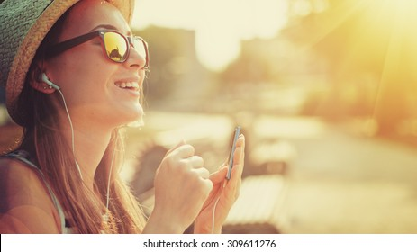 Attractive young woman listening to music on the music player in the city outdoors. Hipster girl enjoying the tunes in her earphones in the morning park. Lens Flare.