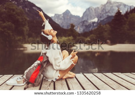 Attractive young woman listening to music via wifi headphones and smartphone on the lake
