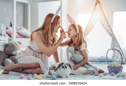 Attractive young woman with little cute girl are preparing for Easter celebration. Mom and daughter wearing bunny ears are having fun with Easter bunny while sitting on the floor at home.