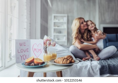 Attractive young woman with little cute girl are spending time together at home while sitting on bed. Happy family concept. Breakfast in bed on Mother's day.