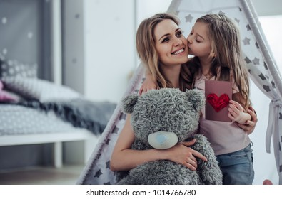 Attractive young woman with little cute girl are having fun together at home. Mom and daughter are sitting on the floor, hugging, kissing and smiling. Happy family concept. Mother's day.