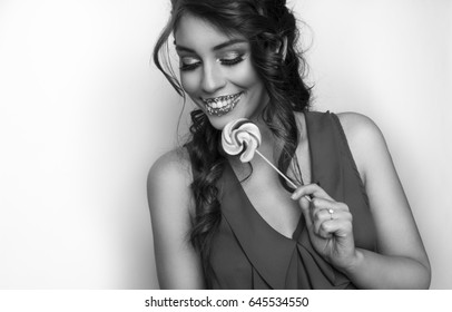 Attractive young woman with lollipop, studio shot, black and white