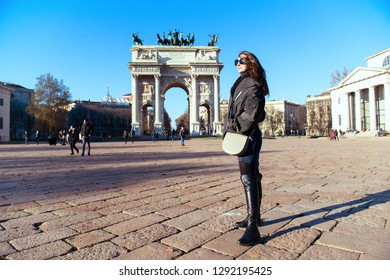 Attractive young woman with long dark hair and sun glasses posing outdoor near Arch of Peace in Milan streets, Italy. Beautiful caucasian model portrait. Steet fashion