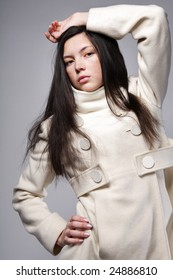 Attractive young woman with long hair posing in white coat.
