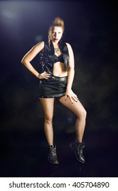 Attractive young woman with long hair and wearing a short black mini skirt to a black leather vest and has supported a hand on her hips