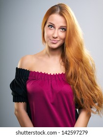 Attractive young woman with long red hair in a red dress. Isolated on a gray background