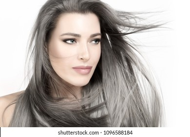 Attractive young woman with long trendy silverhair blowing in a breeze. Beauty portrait isolated on white. Care and hair products concept