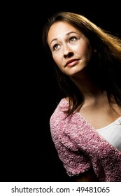 attractive young woman looking up at bright light