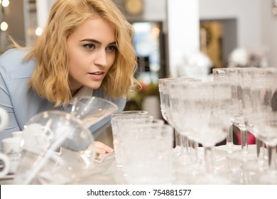 Attractive young woman looking at glassware display at the local houseware store shopping for home accessories dinnerware glassware buying luxury consumerism purchase sale retail discount offer price