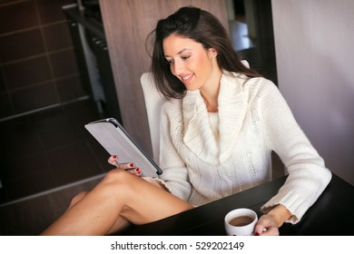 Attractive young woman looking at her tablet computer with a cup of coffee in her hand