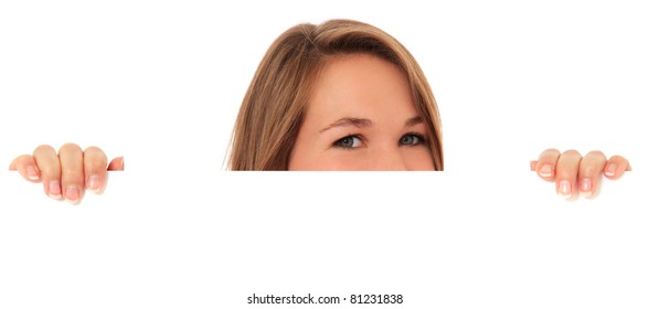 Attractive young woman looking over white wall. All on white background.