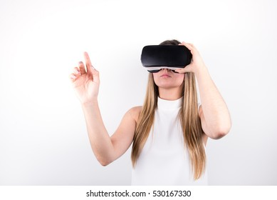 attractive young woman looking through virtual reality headset, pointing up, indoor shot over white background. caucasian female model wearing VR goggles.