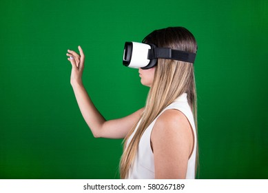 attractive young woman looking through virtual reality headset, pointing up, green screen background