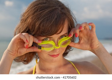 Attractive young woman looks at camera through a Swimming Goggles