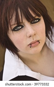 Attractive young woman with lots of eyeliner and lip piercings