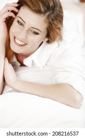 Attractive young woman lying on her bed at home relaxing