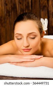 Attractive young woman lying on her stomach in spa with a flower in hair