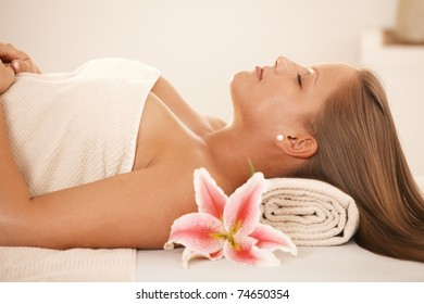 Attractive young woman lying on massage bed at spa, sleeping.?
