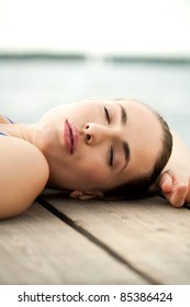 attractive young woman lying in swimsuit on wooden planks