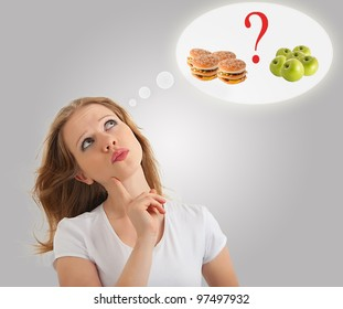 attractive young  woman makes a choice between healthy and unhealthy foods, apple and hamburger on a modern conceptual background