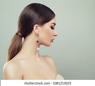 Attractive Young Woman with Makeup, Healthy Ponytail Hairstyle and Earrings with Pearls
