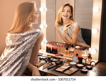 Attractive young woman with makeup made by professional artist looking in mirror indoors