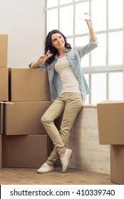 Attractive young woman is making selfie and smiling, standing among cardboard boxes, ready to move